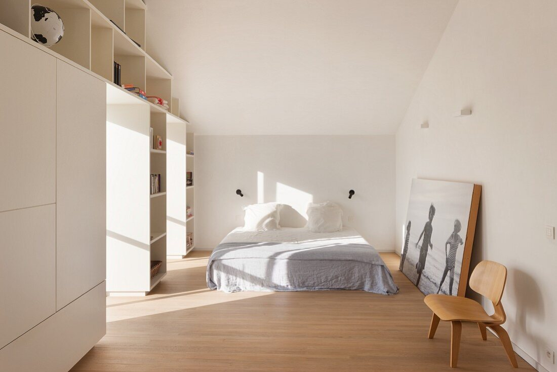 White fitted wardrobes in simple attic bedroom with parquet floor