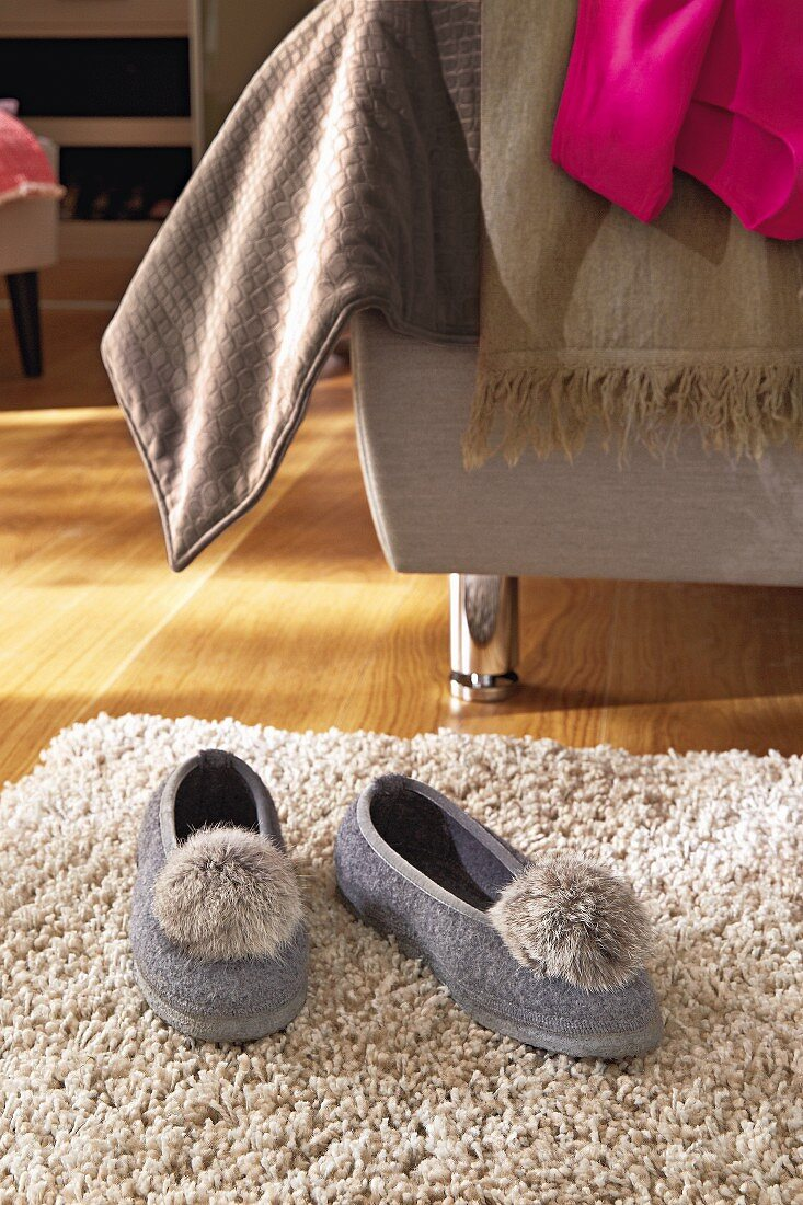 Slippers with pompom toes on rug next to bed with various blankets
