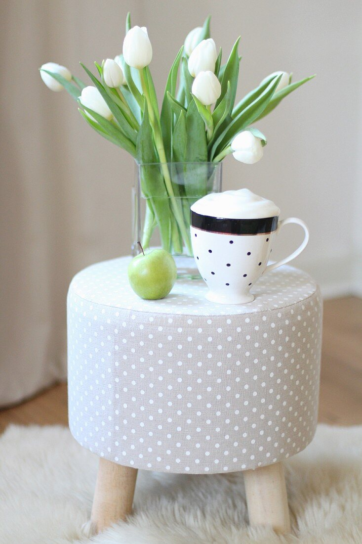 Cup of cappuccino and vase of white tulips on grey polka-dot stool