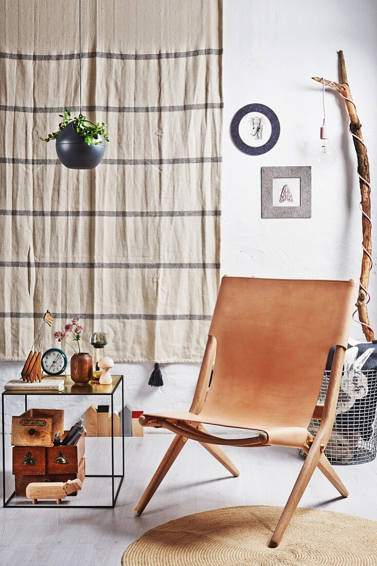 Leather chair and side table in front of beige wall hanging and standard lamp made from branch with bulb socket