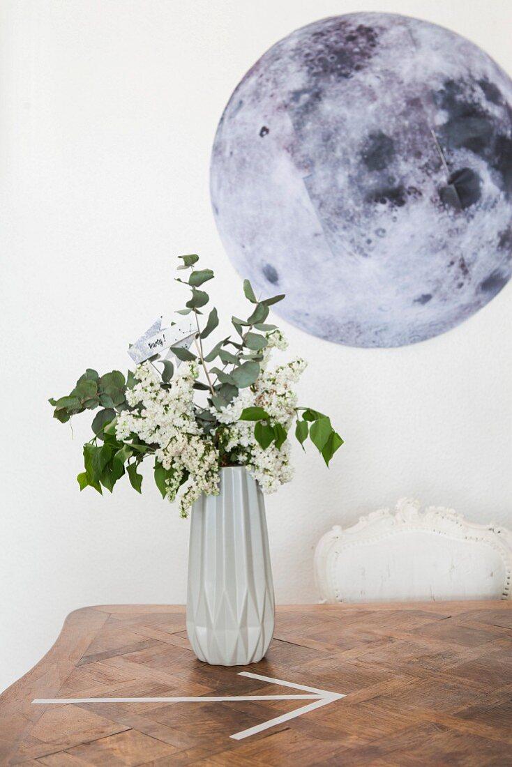 Vase mit geometrischer Form, dahinter ein Mond-Bild