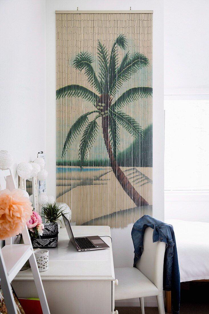 White desk and chair in front of bamboo wall hanging with palm tree motif