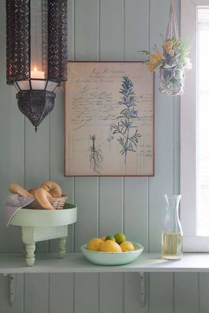 Croissants, fruit and carafe on bracket shelf on board wall
