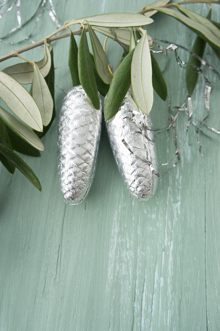 Pine cones covered in silver foil and lametta hanging from olive branch