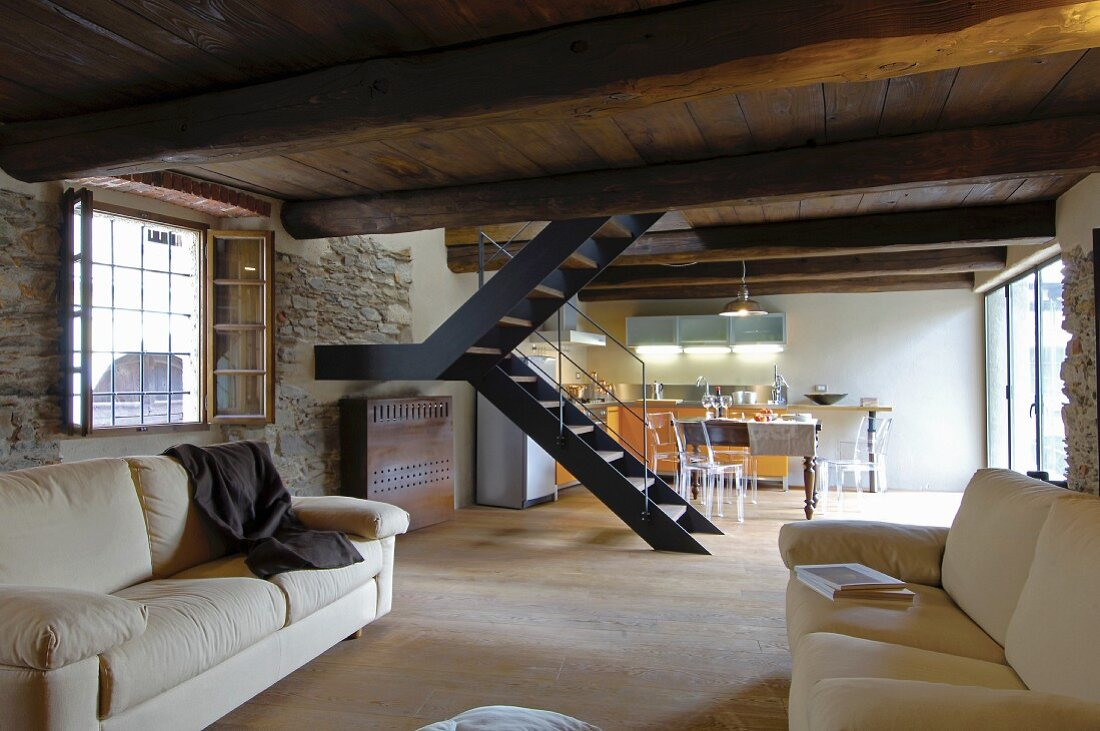 Wooden ceiling with massive beams and stone wall in rustic living room with staircase and kitchen-dining room in background