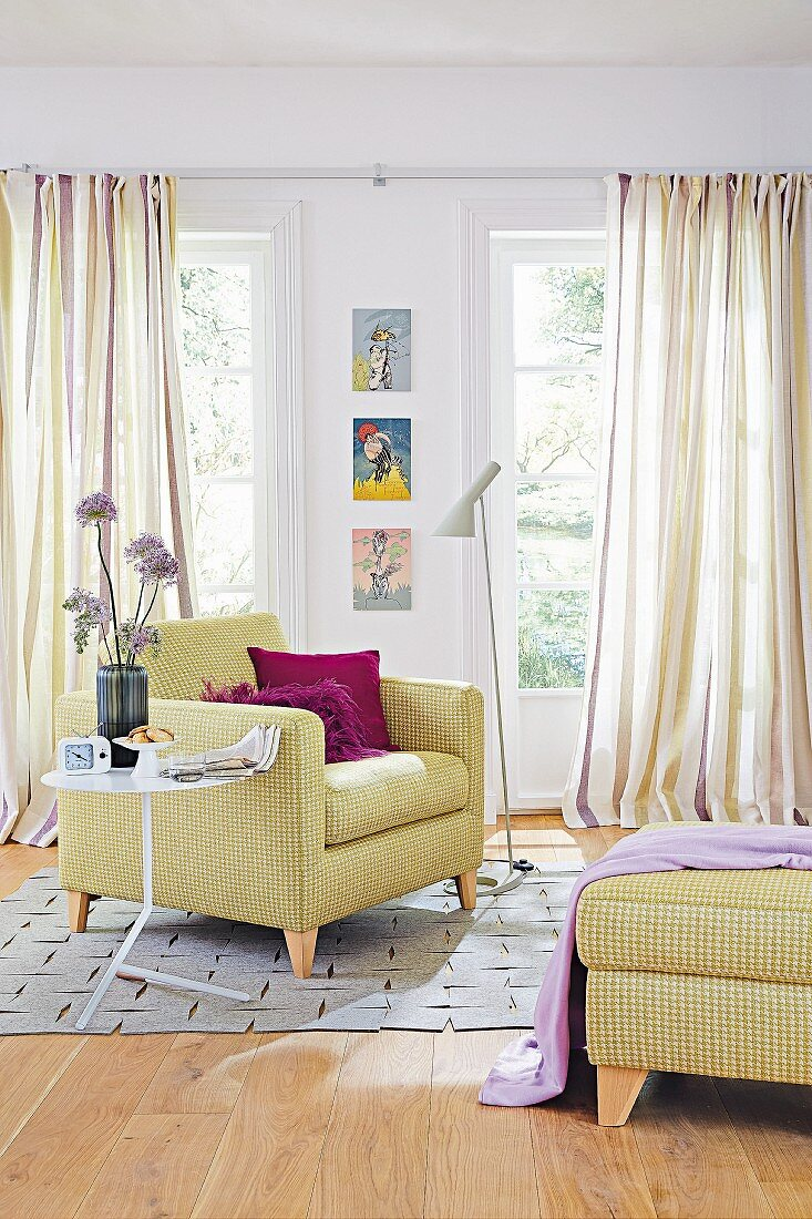 An upholstered armchair and a pepita-patterned footstool against striped curtains in a living room in lilac and delicate green