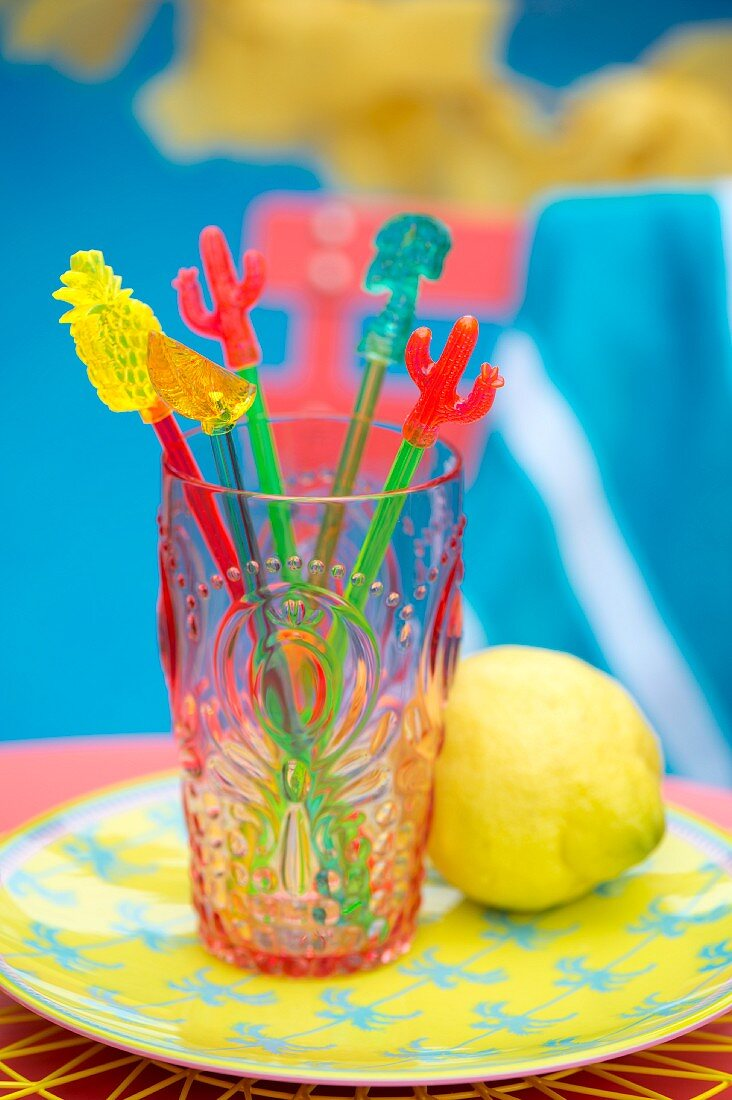 Colourful swizzle sticks in plastic beaker on plate