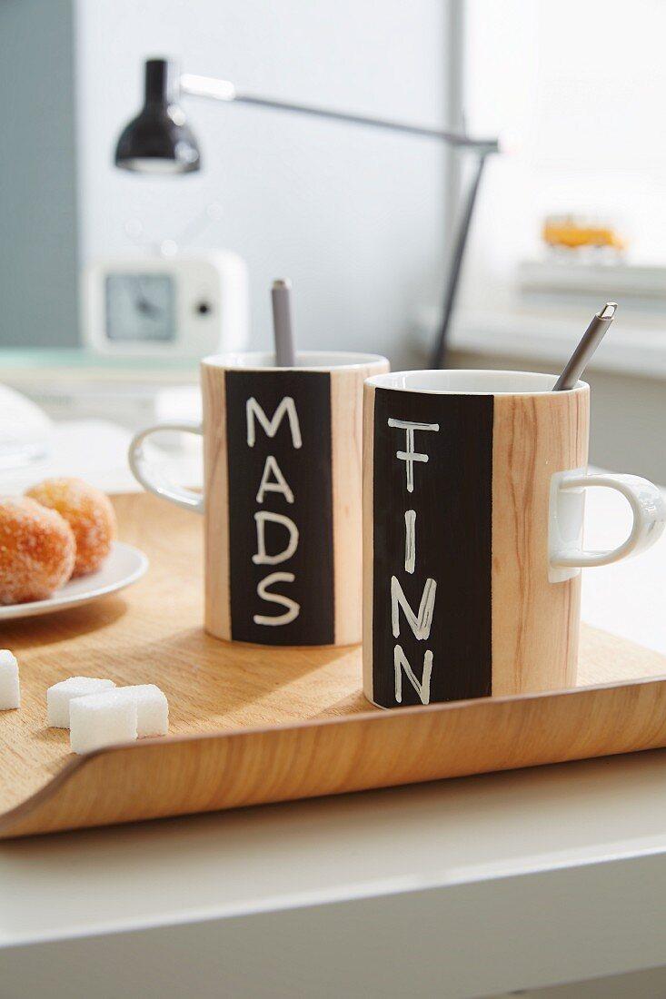Wood-effect mugs with names written on chalkboard stripes