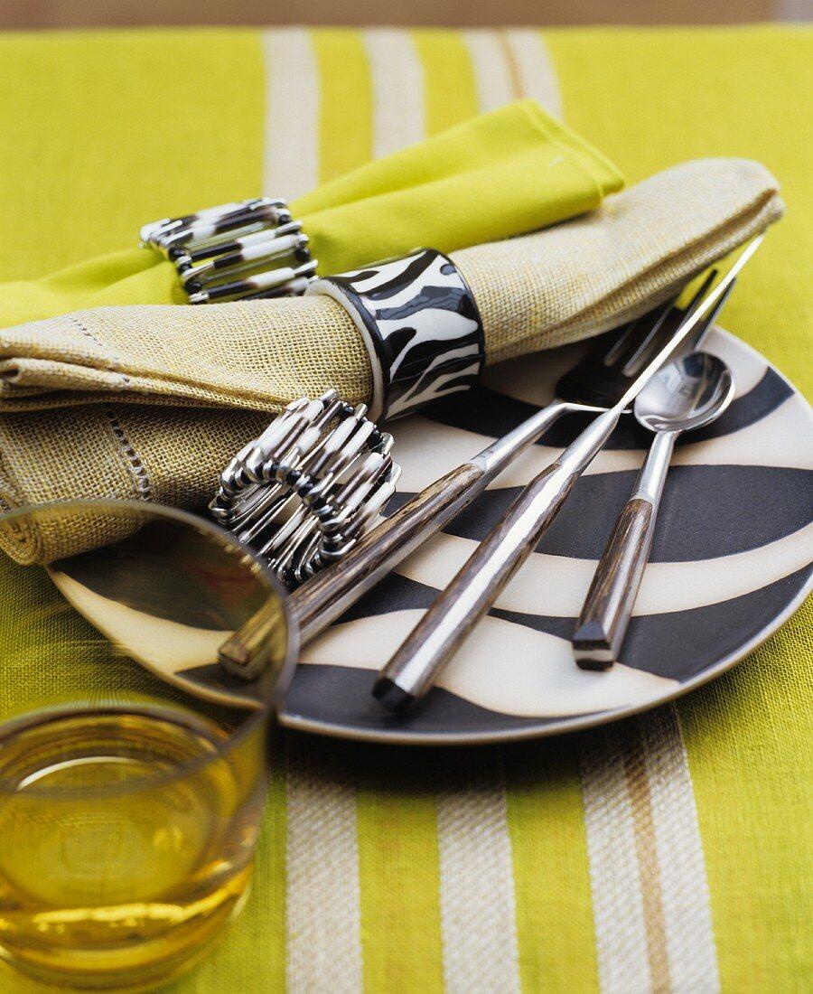 Schwarz-weißer Teller mit Besteck und Stoffservietten
