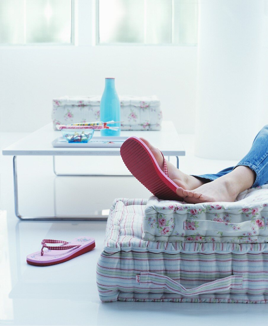 Woman's feet in red flip-flops on floor cushions with romantic floral pattern and striped pattern in pastel shades