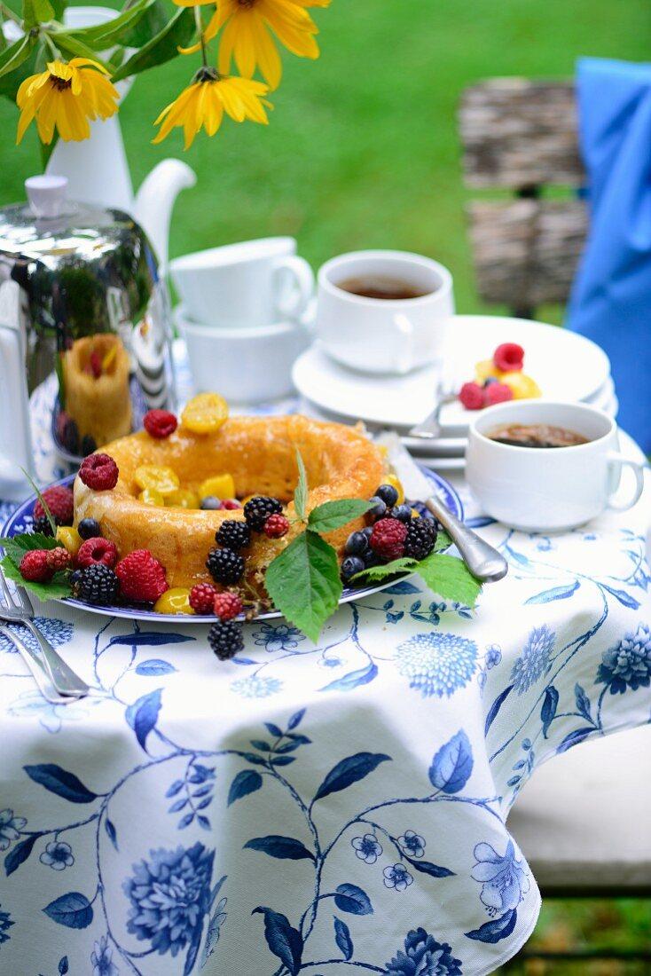 Baba au Rhum mit frischen Früchten auf sommerlichem Tisch im Freien