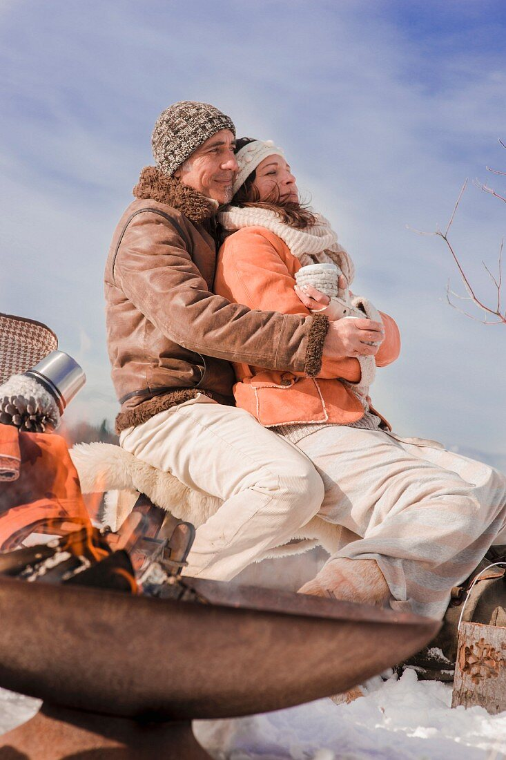 Man and woman cuddling during a winter picnic in a snowy landscape