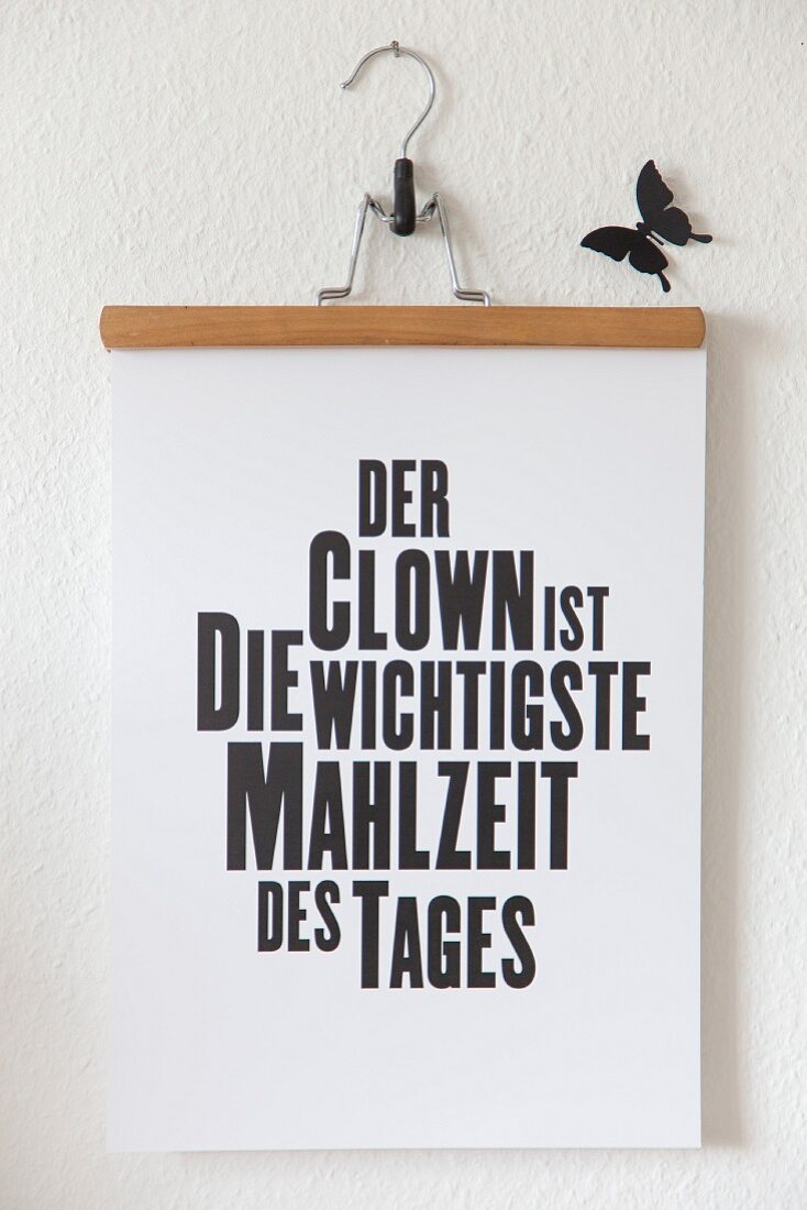 Artwork with motto hanging from trouser hanger and black butterfly decoration on white wall