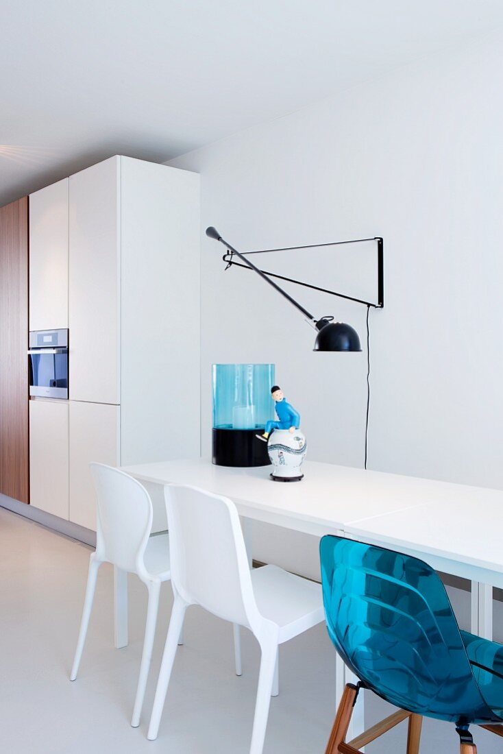 Modern white table and various chairs in open-plan kitchen