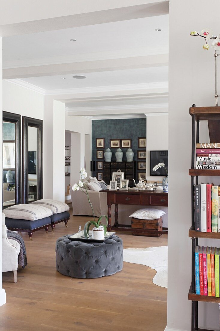 View through wide, open doorway into living room with grey, upholstered pouffe on wooden floor