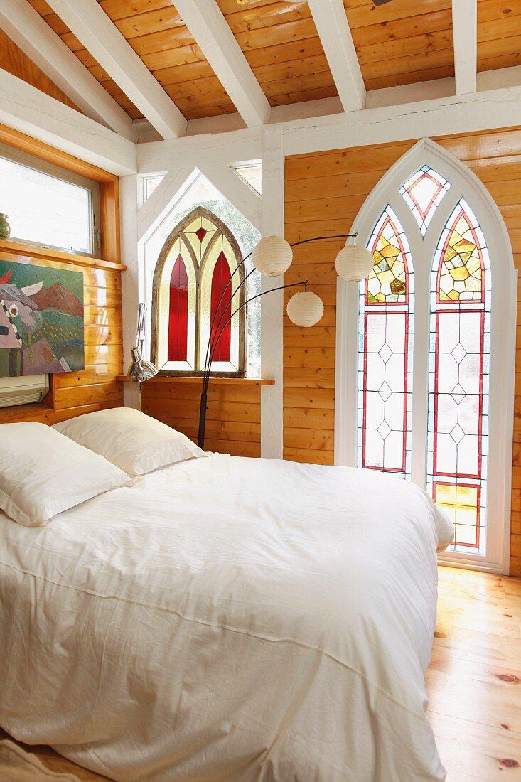 weiße Balken und Naturholz im Kontrast zu gotischen Formen und farbiger Bleiverglasung in künstlerisch inspiriertem Schlafzimmer in Taos (New Mexico)