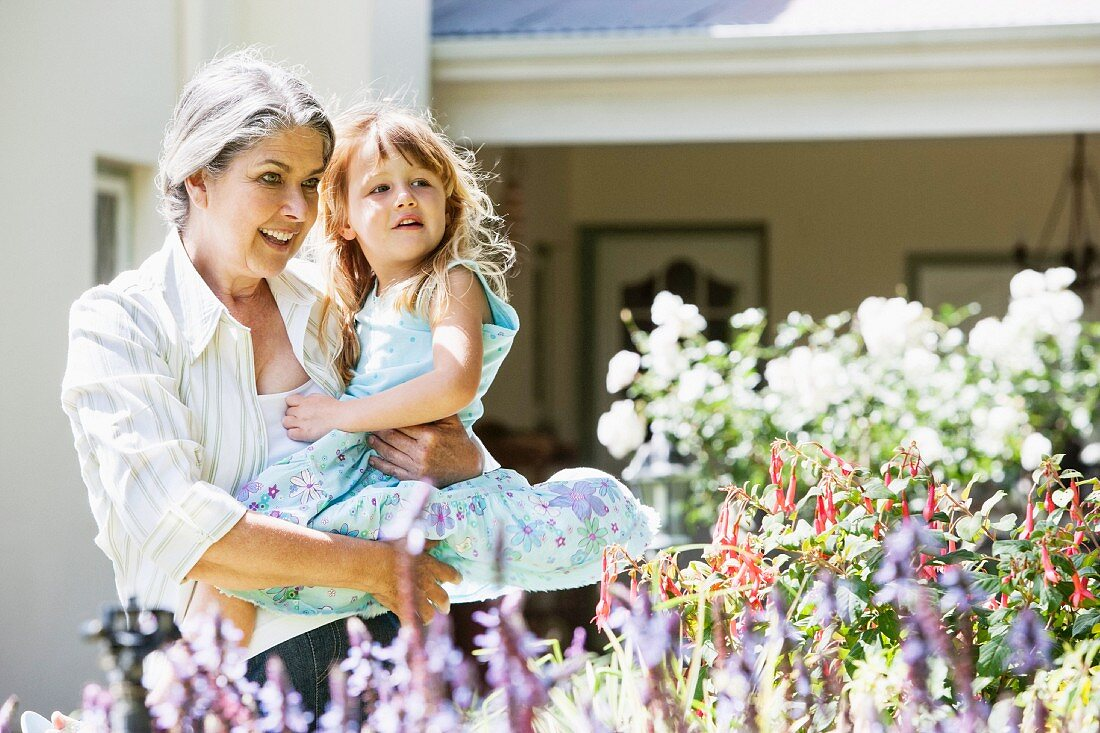Grandmother and granddaughter admiring flowers