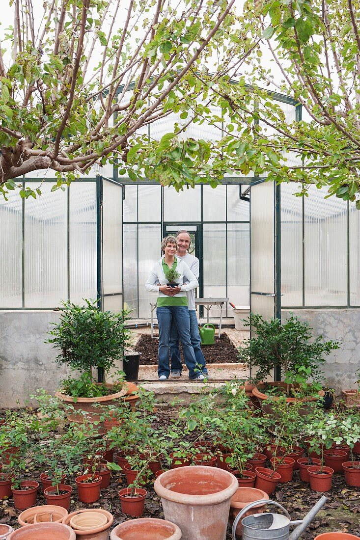 Couple smiling in greenhouse