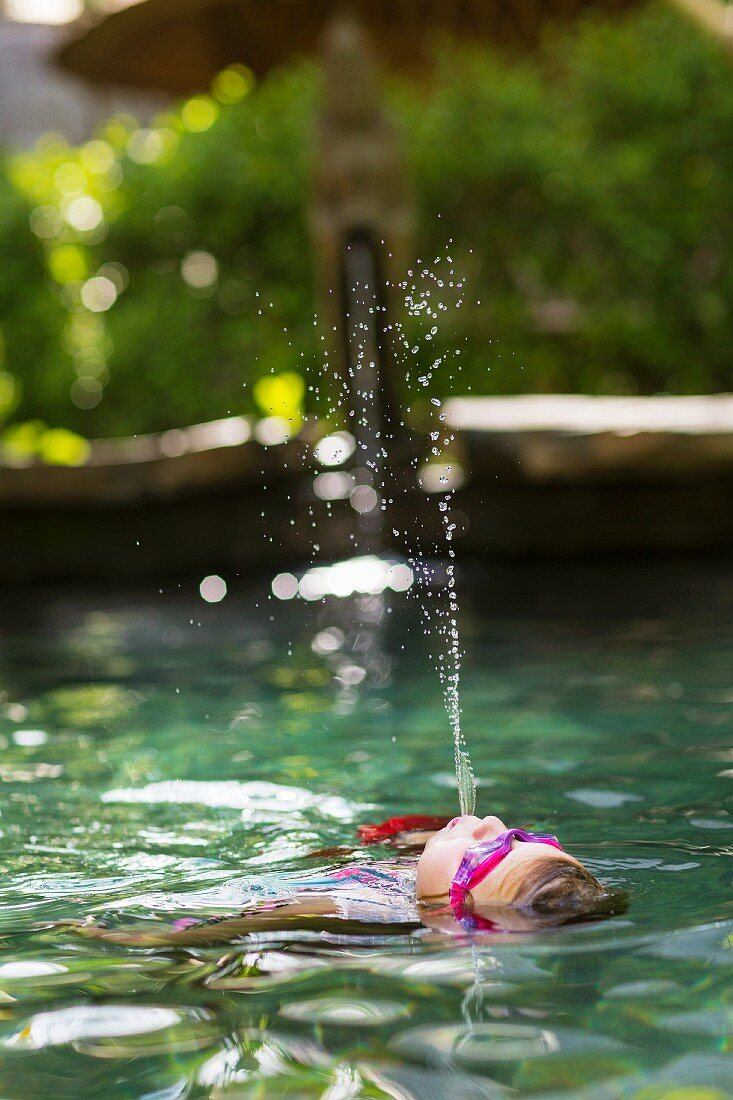 Girl spraying water in swimming pool
