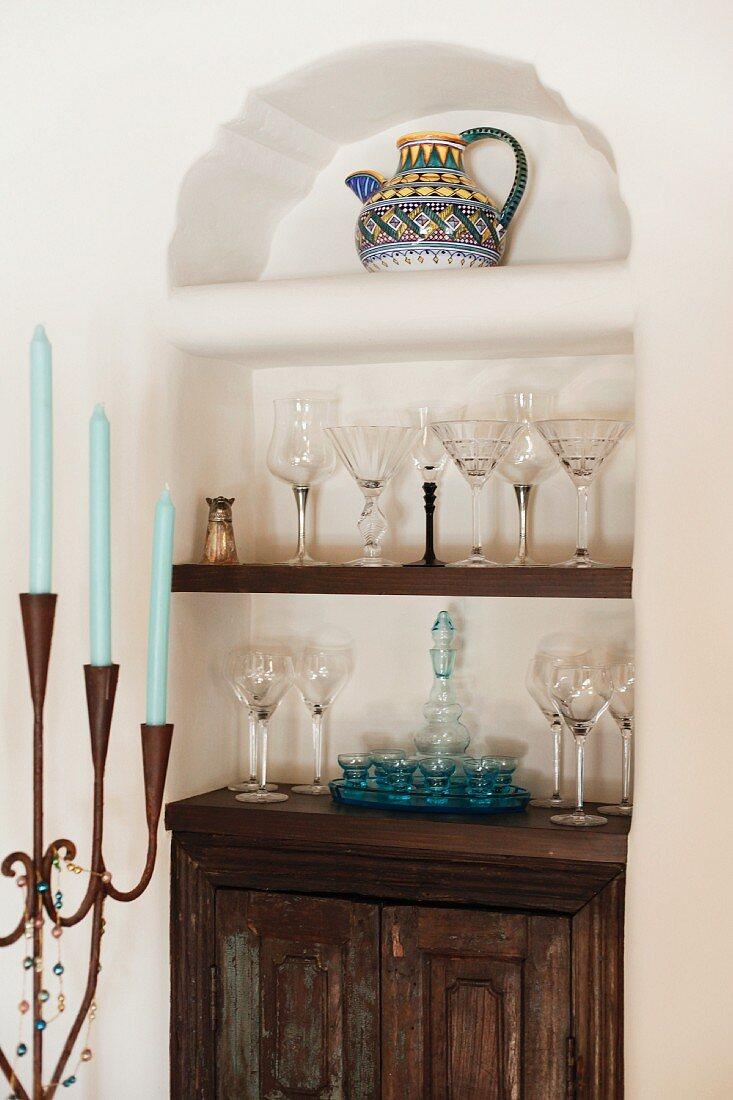 Holzschränkchen & Regalböden mit dekorativen Gläsern in Wandnische