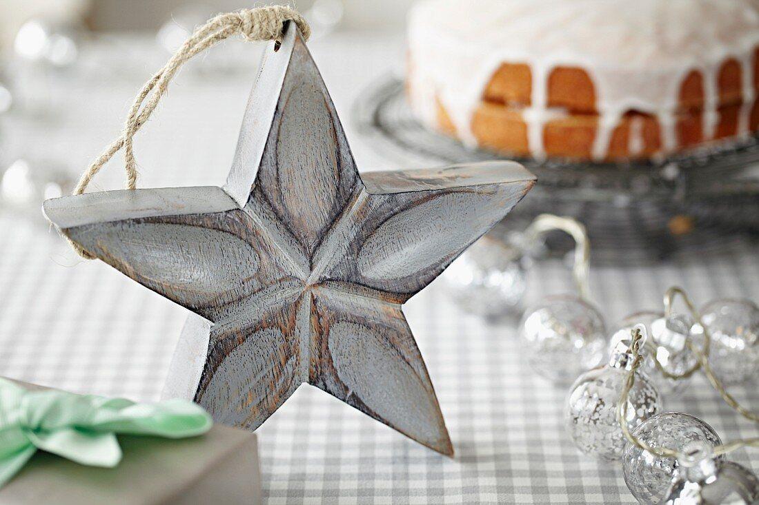 Weiß bemalter Holzstern auf Tisch vor glasiertem Kuchen