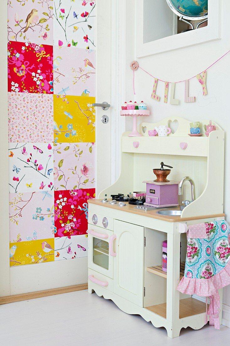 White toy kitchen next to interior door covered in bright, patchwork pattern