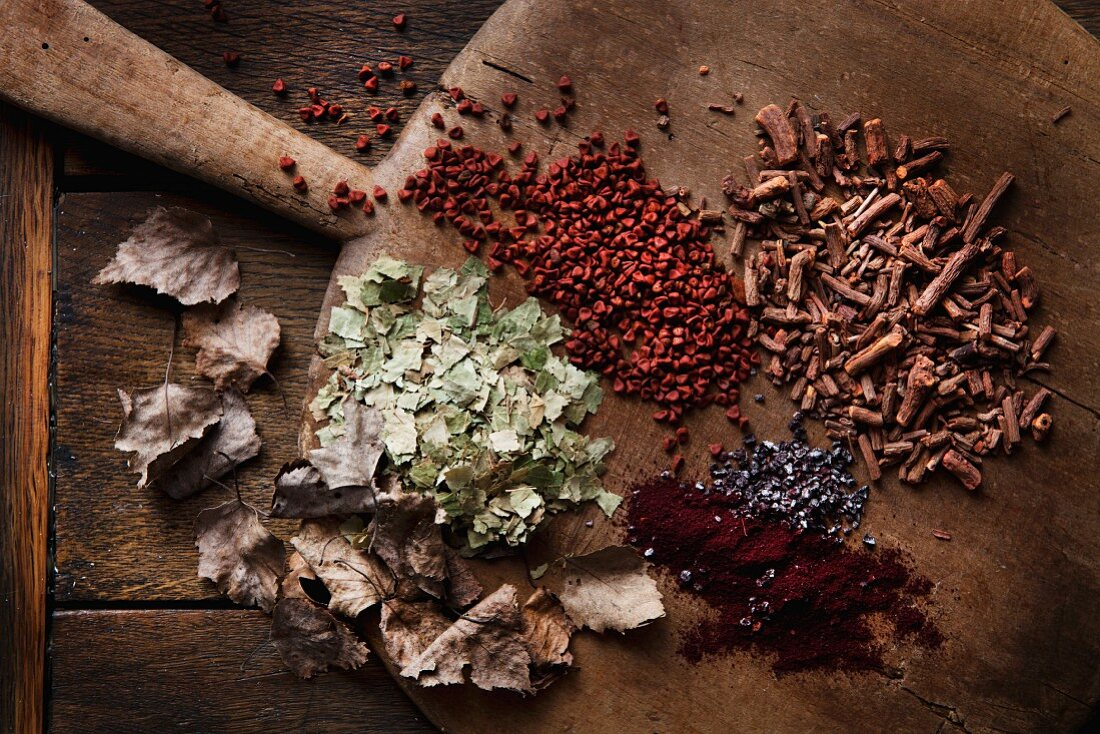 Various materials used to dye eggs laid out on old wooden board; dried birch leaves, cochineal, reddish seeds