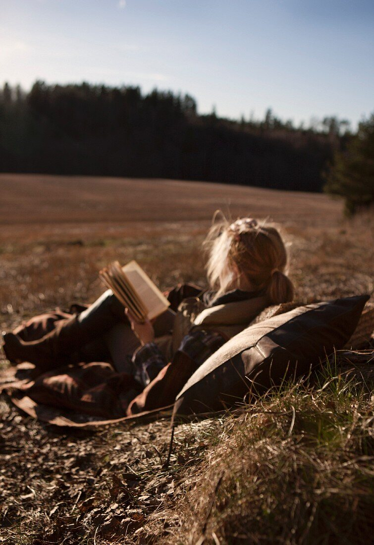 Woman reading on comfortable blanket in autumn meadow