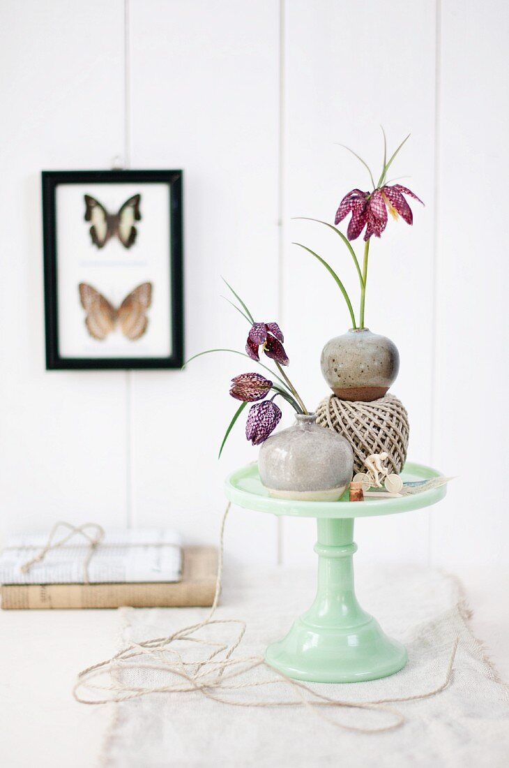 Snake's head fritillaries in small stoneware vases on cake stand made from pale green porcelain
