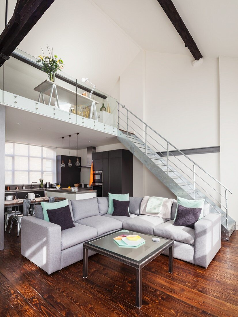 Coffee table and grey corner sofa in open-plan, loft-style interior with staircase leading to gallery in background
