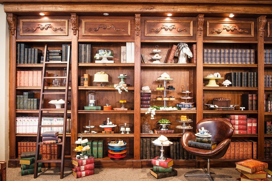 Antique-style, fitted shelves of antiquarian books, cake stands and cake platters