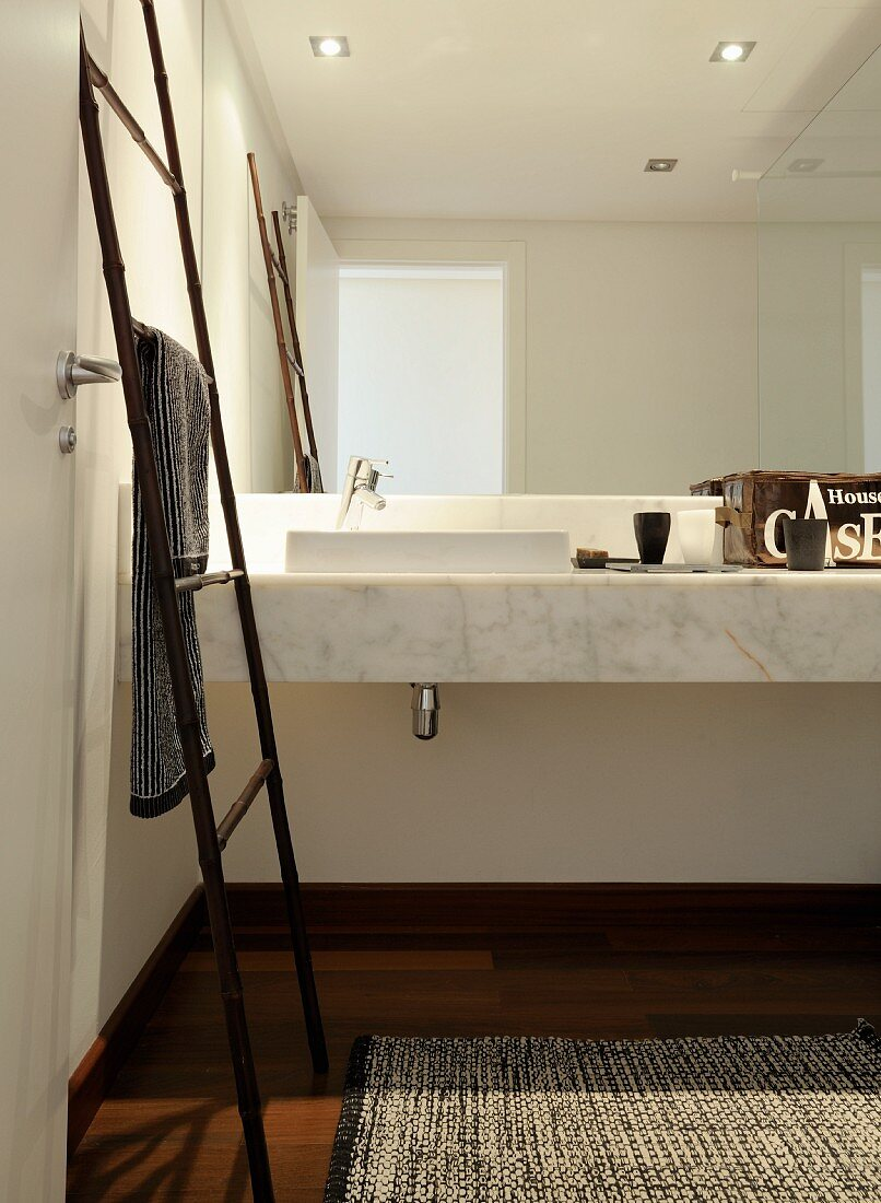Bamboo, ladder-style towel rack in front of marble washstand and mirrored wall