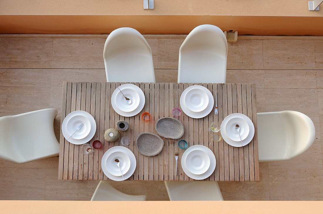 Birdseye view of terrace with simply set wooden table and Panton chairs
