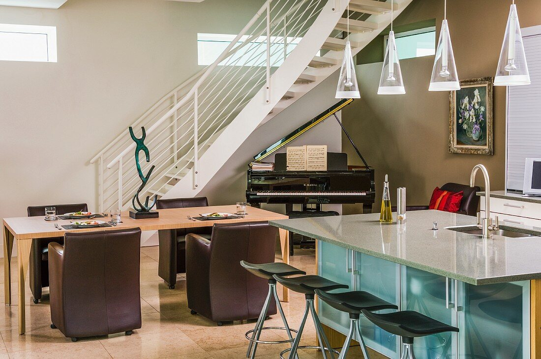 Counter with sink integrated into pale grey stone worksurface, bar stools and dining table with brown leather armchairs in front of white, curved metal staircase above grand piano