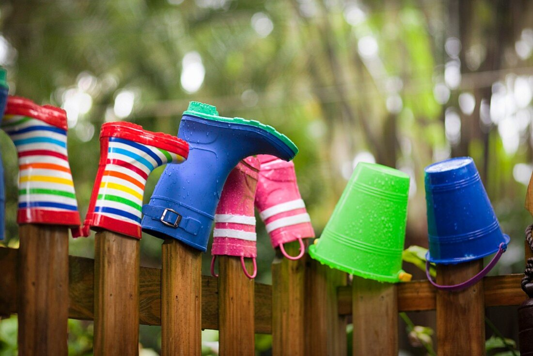 Row of wellington boots and buckets on top of garden fence