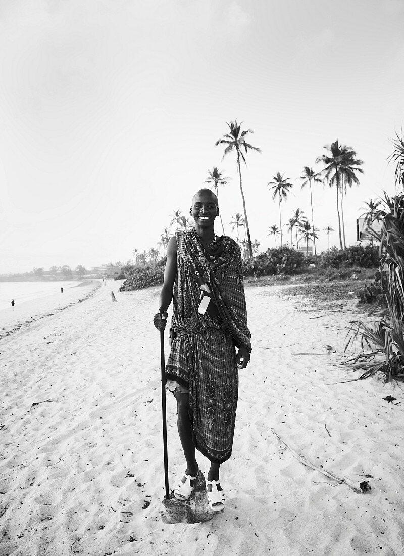 Schwarzweiss-Aufnahme eines Afrikaners in traditioneller Kleidung mit Sandalen am Strand