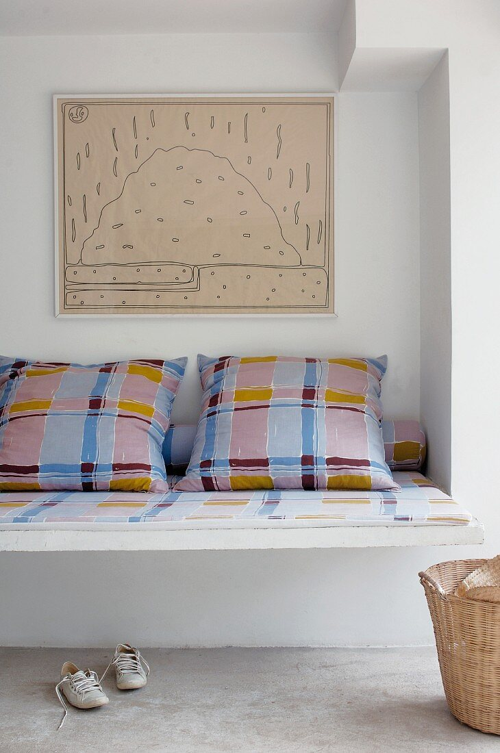 Masonry bench with tartan seat cushion and scatter cushions in niche below framed drawing on wall