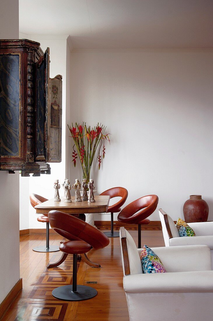 Brown leather swivel chairs and table in window bay in hotel with parquet flooring and white armchairs in foreground
