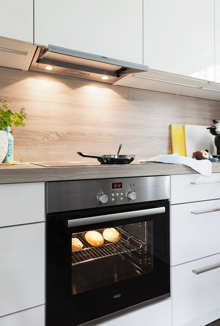 Bread rolls in an illuminated often and a frying pan on a ceramic glass hob in a built in kitchen with white cupboards and a wooden look work surface