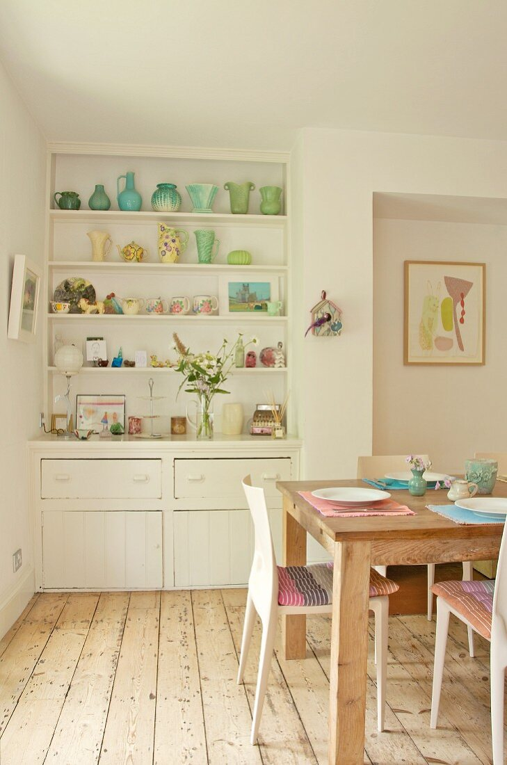 Original kitchen shelving built into niche with collection of 30s vases; wooden table and modern chairs on stripped wooden floor