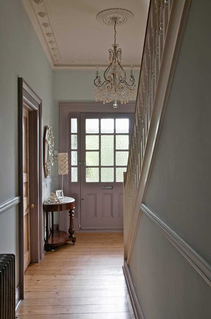 Chandelier hanging from stucco ceiling and staircase in pastel blue hallway of Victorian house