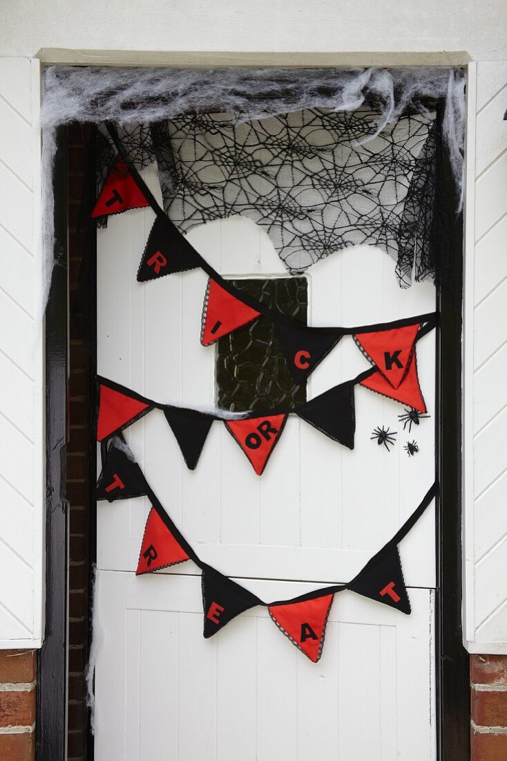 Bunting and spiders' webs on front door as Halloween decorations