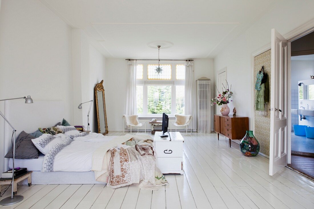 Spacious, retro-style bedroom with white wooden floor; TV on old trunk at foot of bed and door leading to ensuite bathroom