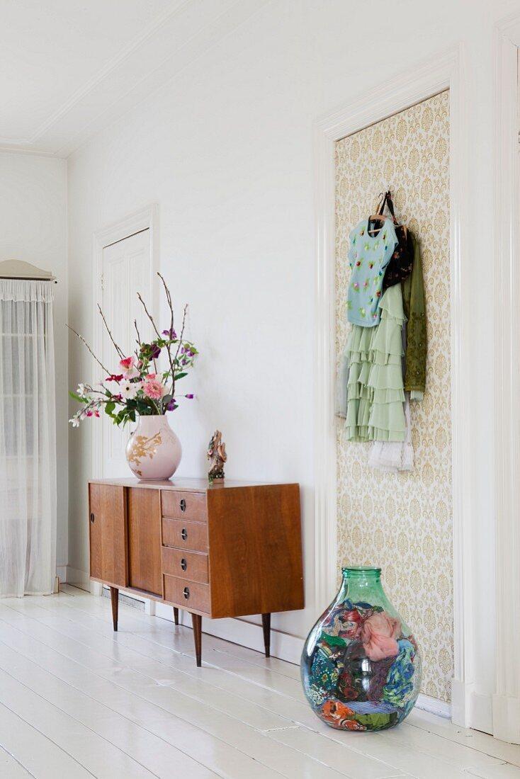 Vase of flowers on 50s, retro sideboard and demijohn full of scarves on floor below coat hooks on wallpapered door