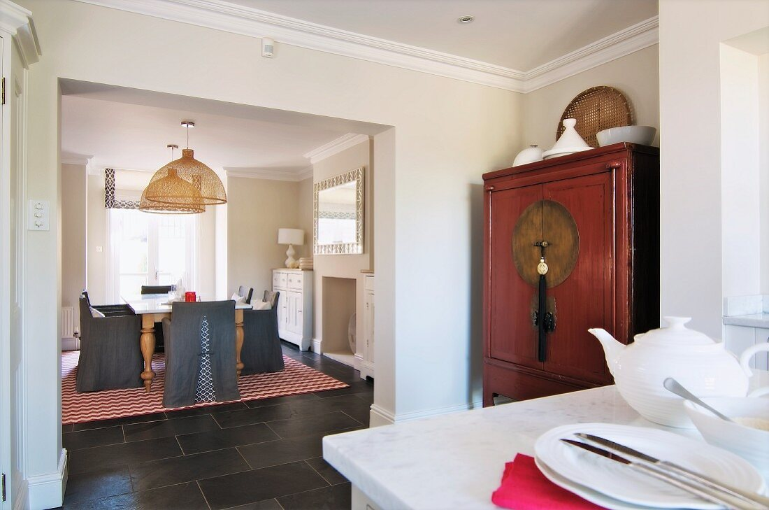 Kitchen with Oriental cupboard in niche; dining area with grey loose covers on chairs and tiled, country-house-style floor