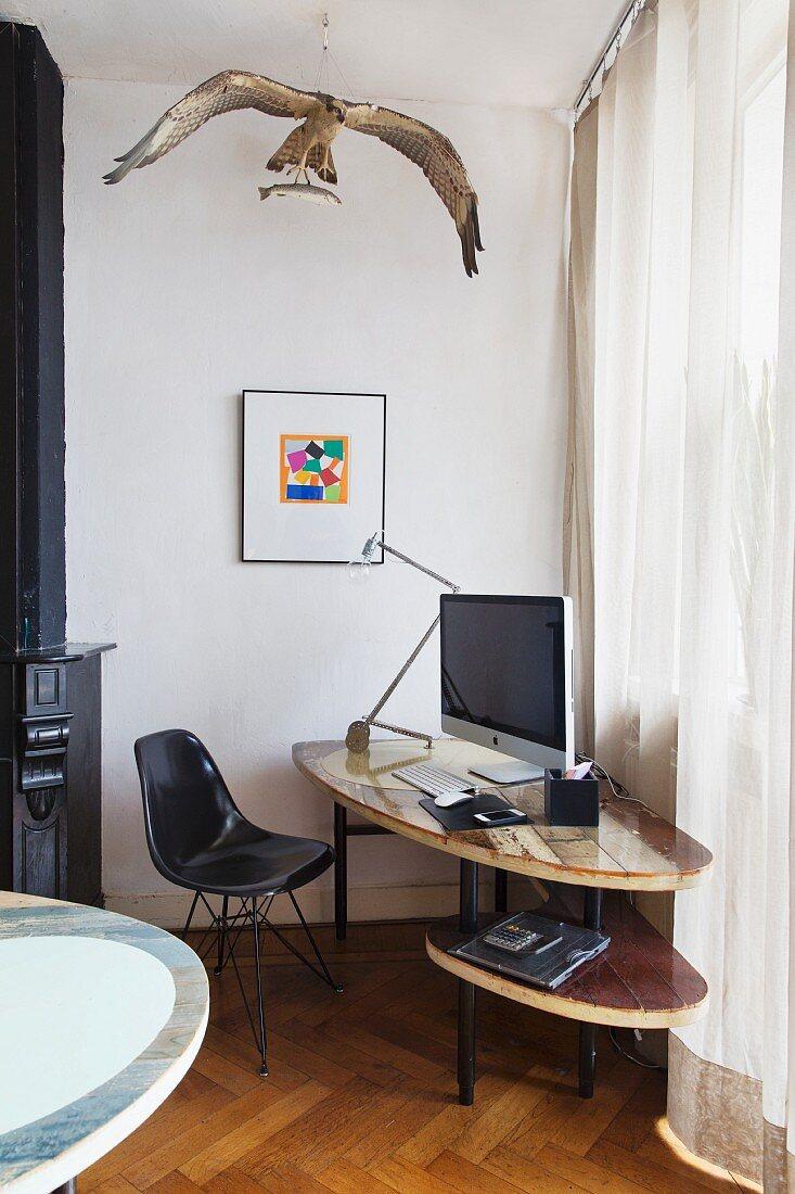 Black, classic-style shell chair at DIY computer desk below stuffed osprey