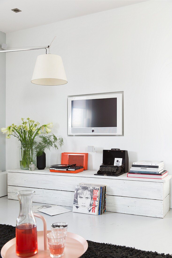 Record player and old typewriter on rustic, white, low sideboard below flatscreen TV mounted on wall