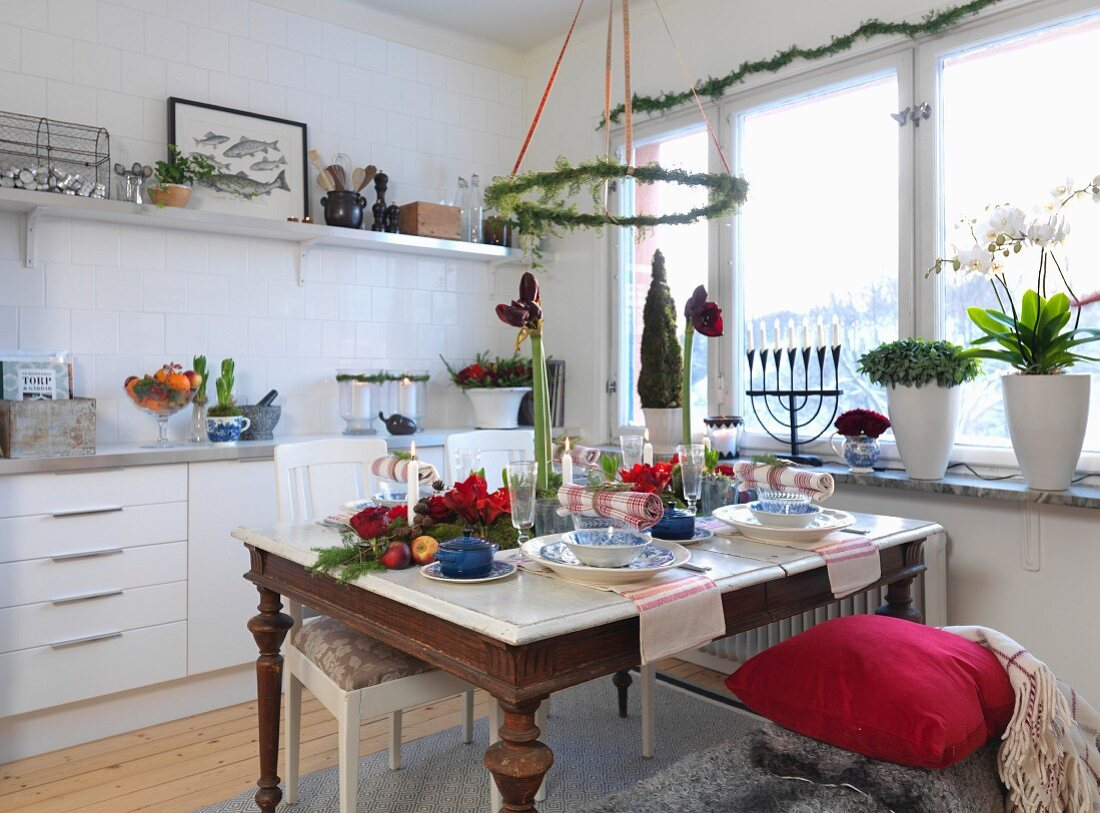 Christmas atmosphere in modern kitchen with Advent wreath above set table