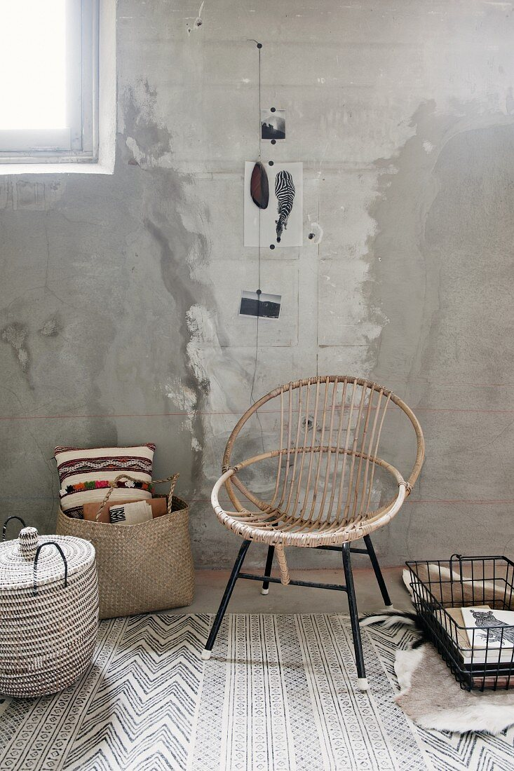 Shell chair made from curved rattan on black metal frame next to bag and basket on patterned rug in industrial, unrenovated interior