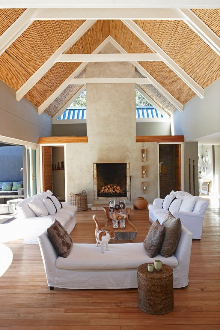 Open-plan interior with sofa set and exposed roof structure with bamboo roof covering in architect-designed house